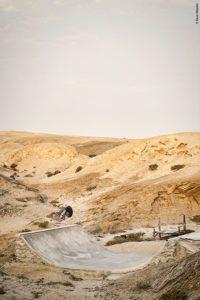 Skater Anthony Lopez en switch frontside flip sur une mini rampe à Nonidas en Namibie