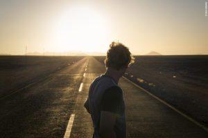 Couché de soleil en Namibie face à une route et Phillip Schuster en premier plan